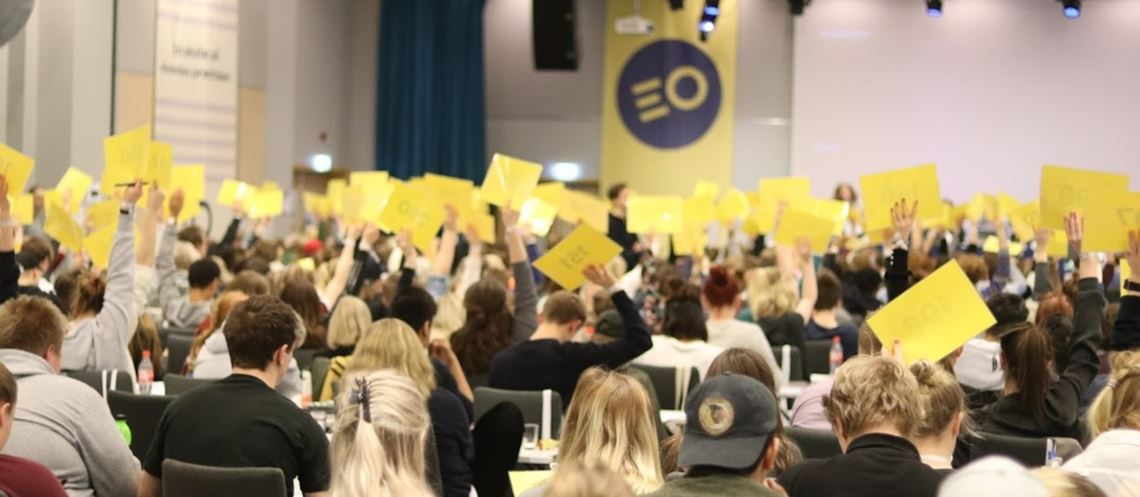 Elever som holder opp gule stemmeskilt i en stor møtesal.
